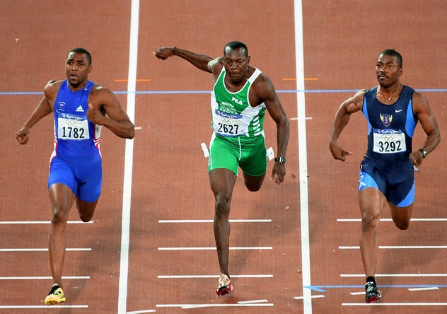 (L to R) Britain's Darren Campbell, Nigerian Aliu Deji and US Curtis Johnson finish their heat 5 of ...