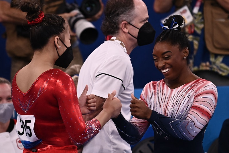 USA's Simone Biles (R) is congratulated by USA's Sunisa Lee after competing in the artistic gymnasti...