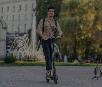 Young man riding electric scooter in the city center