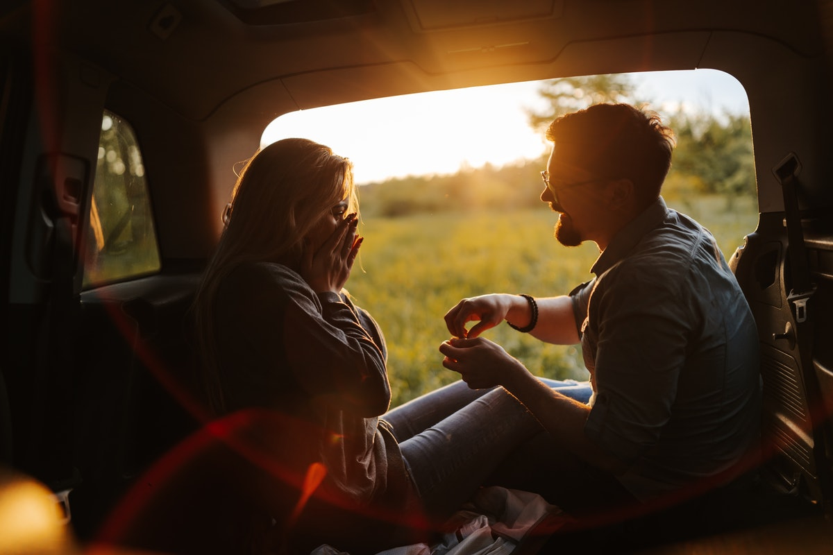 Romantic young couple sitting in open car trunk, enjoying sunset in spring nature while taking a bre...