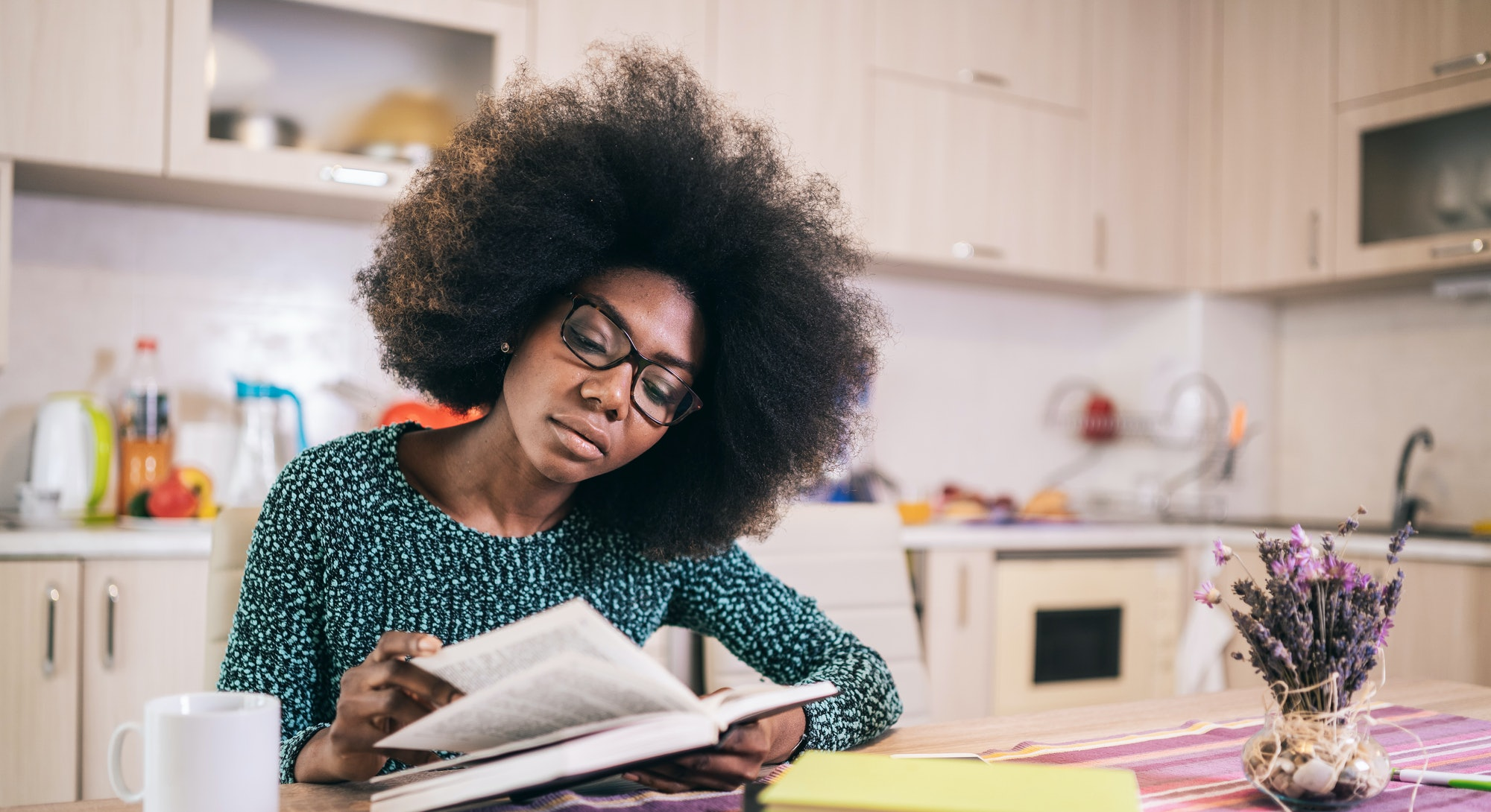 Portrait of attractive african american young woman sitting in the kitchen reading book
