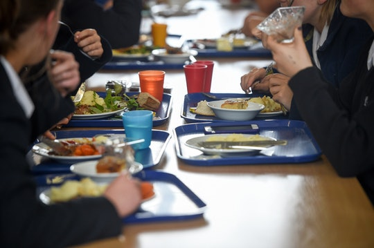 Students eat their school dinner from trays and plates during lunch in the canteen at Royal High Sch...