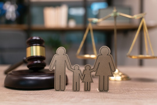 A paper cutout of a family of four is displayed near a judge's gavel and scales to represent family ...
