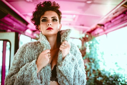 Sensual young sexy woman wearing just lingerie and fur coat in old bus.