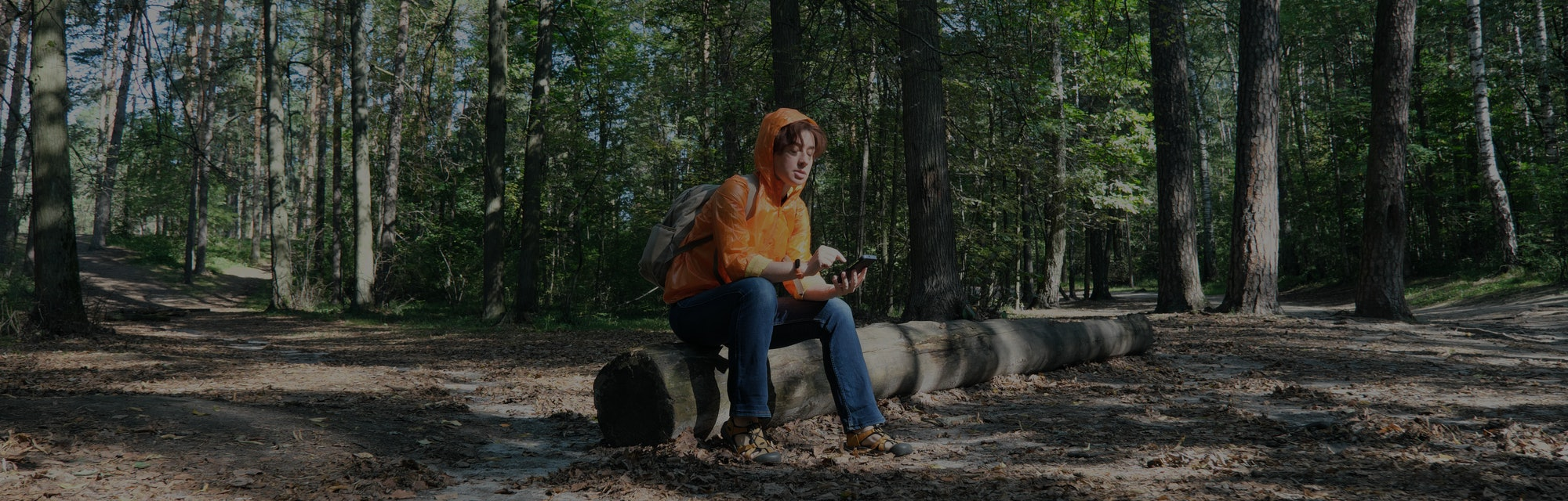 Mature woman hiking in forest is trying to get the direction using GPS in her smart phone