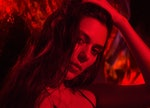 woman lit by red light, running fingers through hair as she peers into camera and reflects on the me...