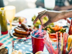 Hand of Black woman picking up a American flag stick from red solo cup on picnic table