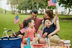 Young Miami family with 4 and 6 year old children holding American flags while enjoying weekend picn...