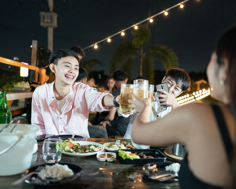 Group of young Asian friends having party drinking beer and eating Thai food in outdoors restaurant,...
