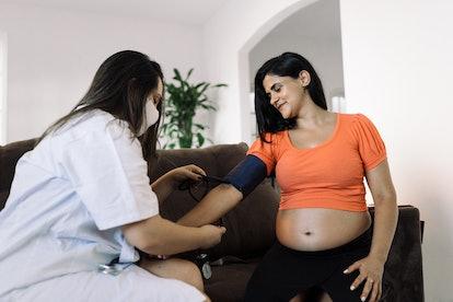 Home nurse measuring blood pressure of pregnant woman