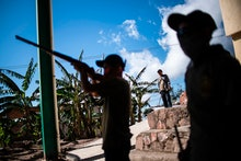 A boy aims a rifle as the Regional Coordinator of Community Authorities (CRAC-PF) community police f...
