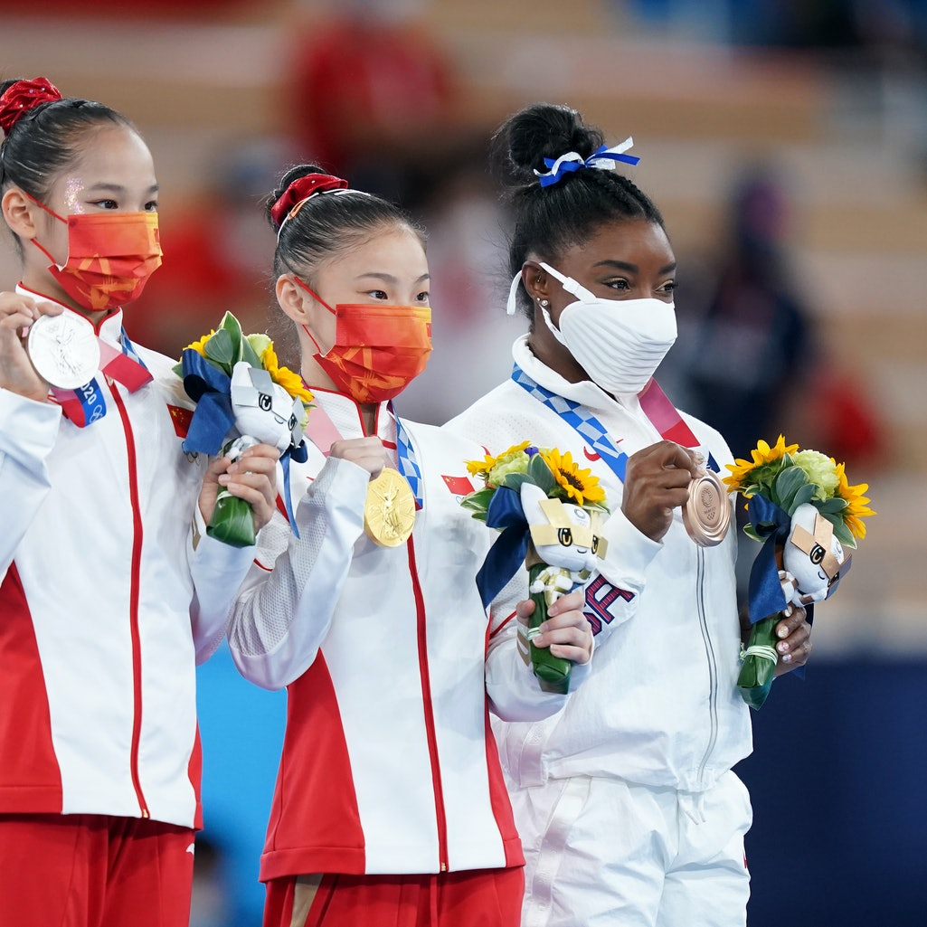 Xijing Tang, Chenchen Guan, and Simone Biles pose together after accepting their medals in the women...
