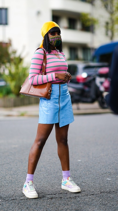 A young Black woman wears an asymmetrical blue leather skirt paired with a green and pink striped to...