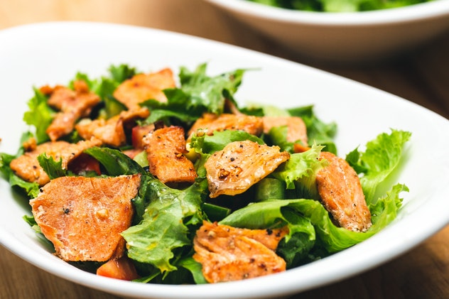 A white bowl of seared salmon fillet salad photography