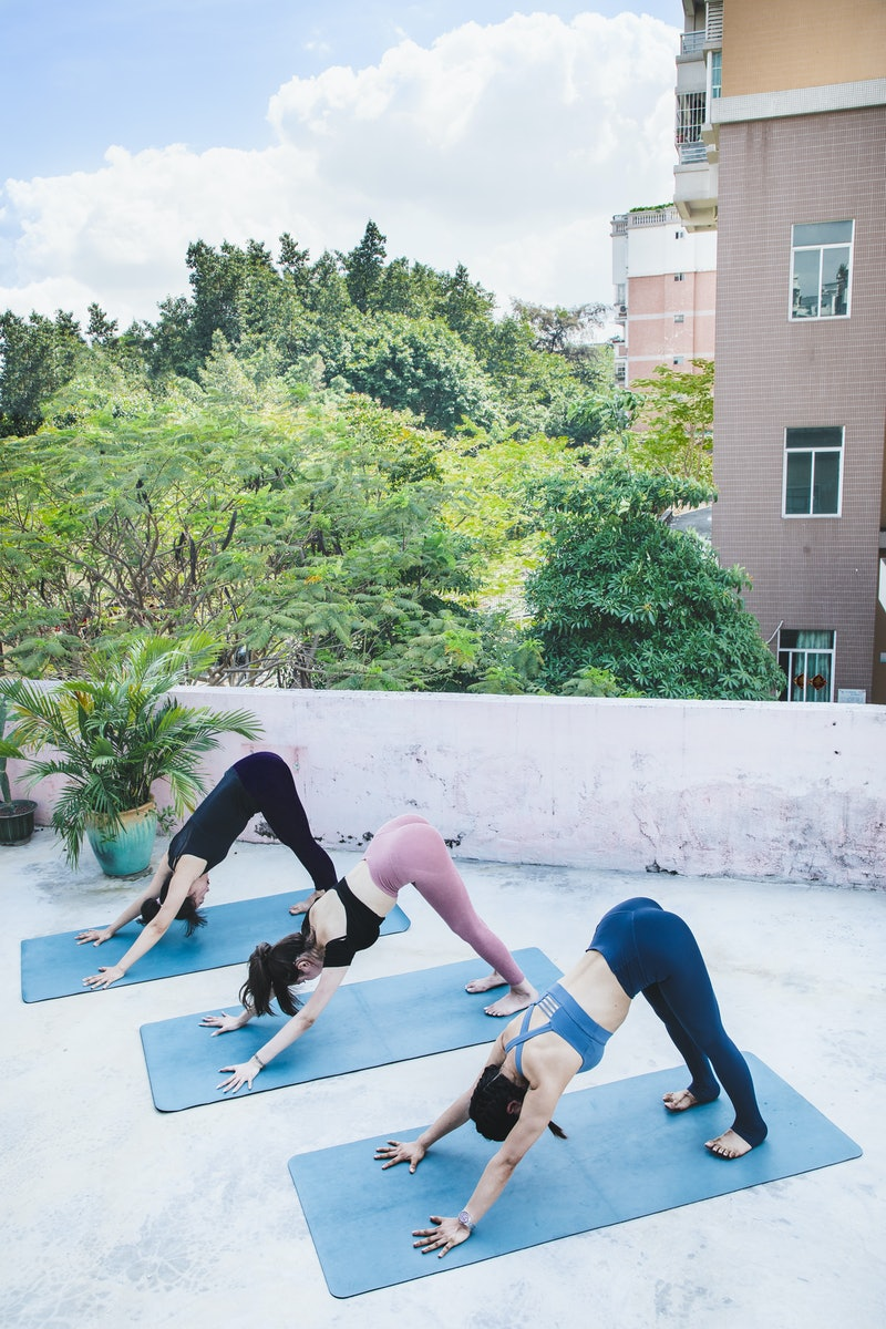 Three women practicing yoga on the rooftop in downward facing dog pose. Peloton instructors explain ...