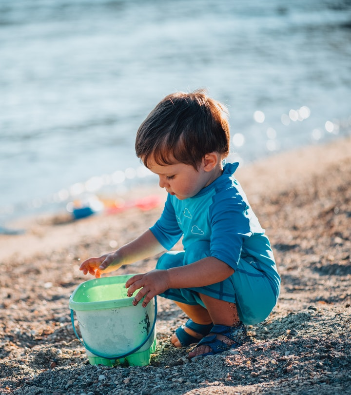Baby Boy Plays With Toy Bucket in the Sea