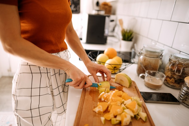 Young woman preparing fruits for healthy meal