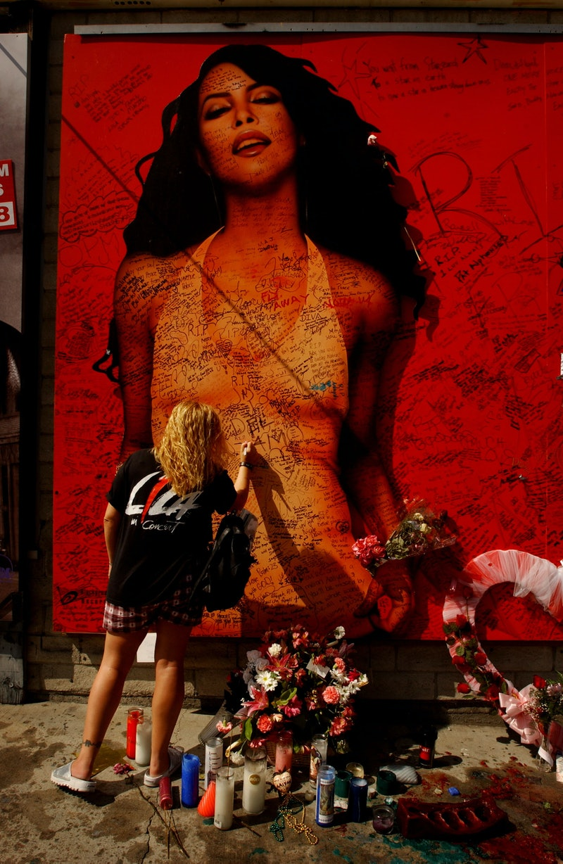 A fan writes a message on a billboard of the late singer and actress Aaliyah August 28, 2001 on Suns...