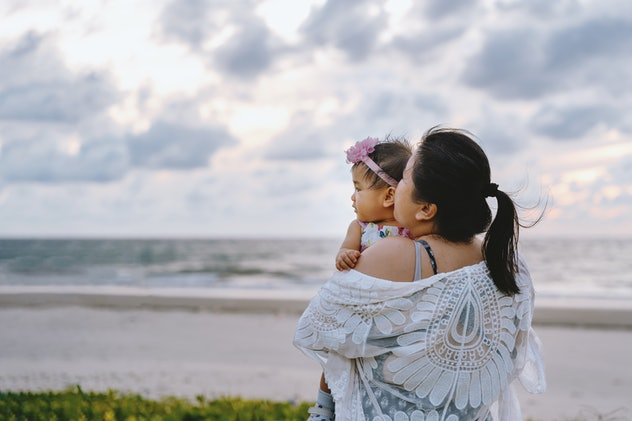mother and baby girl by the ocean