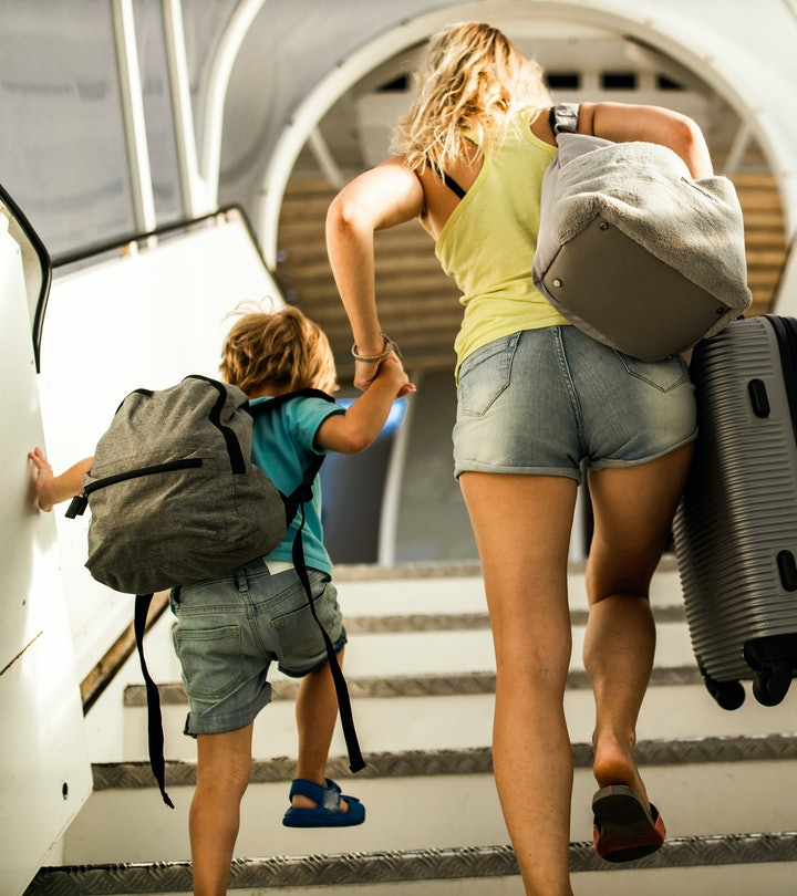 Back view of little boy and his mother holding hands and boarding the plane.