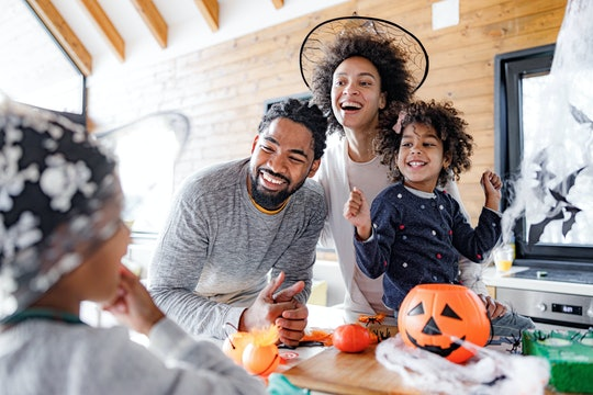 Happy African American family talking while having Halloween celebration at home.