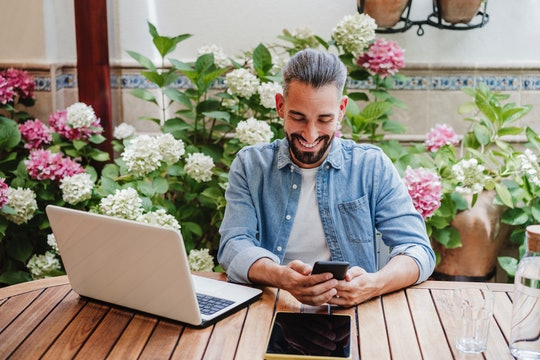 man looking at phone while on laptop