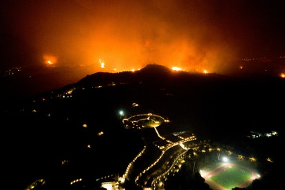 TOPSHOT - A wildfire approaches the Olympic Academy in ancient Olympia in western Greece on August 4...