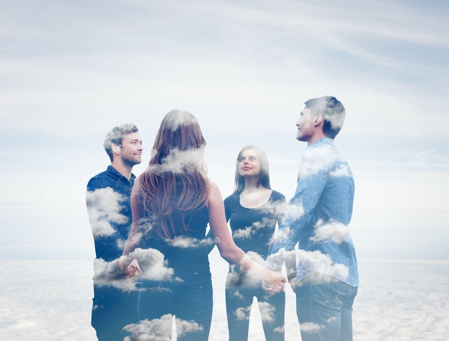 Double exposure of four friends holding hands with clouds.
