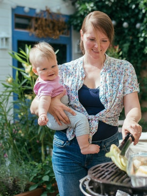 Smiling woman holding her daughter while doing vegan bbq at home outdoor.