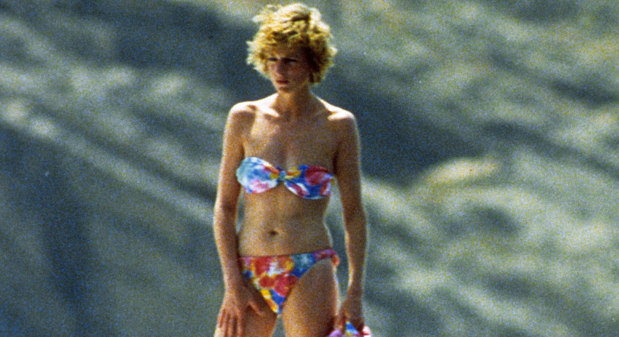 Diana, Princess of Wales, wearing a patterned bikini and holding a matching sarong, stands on board ...