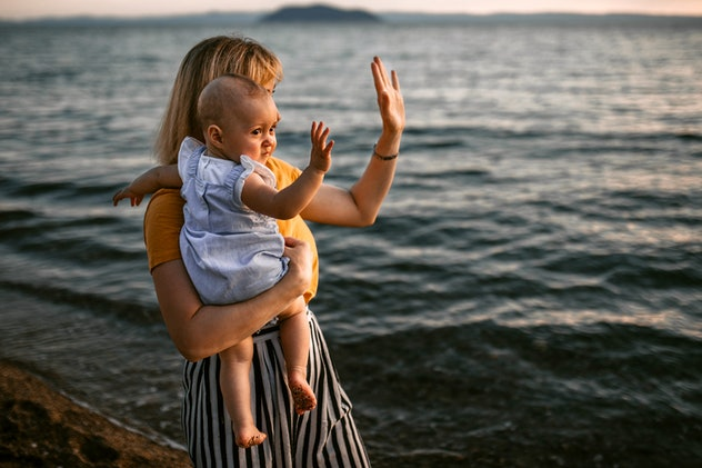 Mother and baby girl enjoy coastal walk and beautiful sunset on the sandy beach, waving to the boats