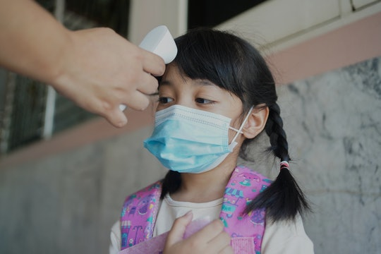 Temperature screening and medical check at school.Teacher with thermometer at preschool entrance che...