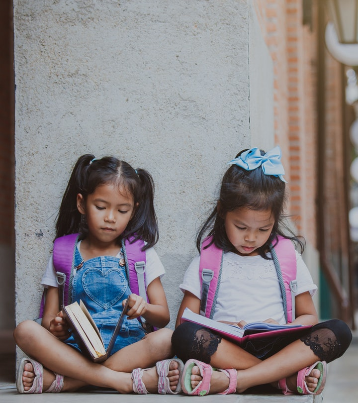 Twin girls sitting next to each other on the ground reading books