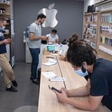 Iranian staff use their smartphones at an apple shop in northern Tehran on June 19, 2021. - Ultracon...
