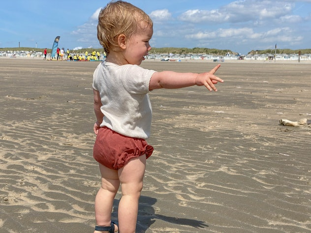 Baby girl at the IJmuiden beach on a warm sunny day