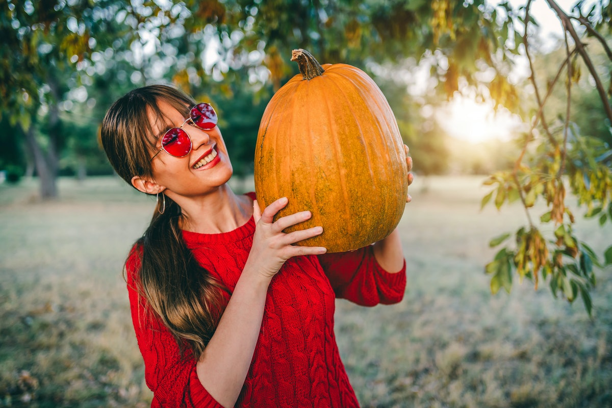 Young smiling woman holding pumpkin for Halloween outdoors during the 2021 fall equinox, which will ...