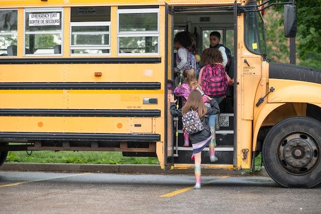 Kids wearing backpacks, getting on a school bus.