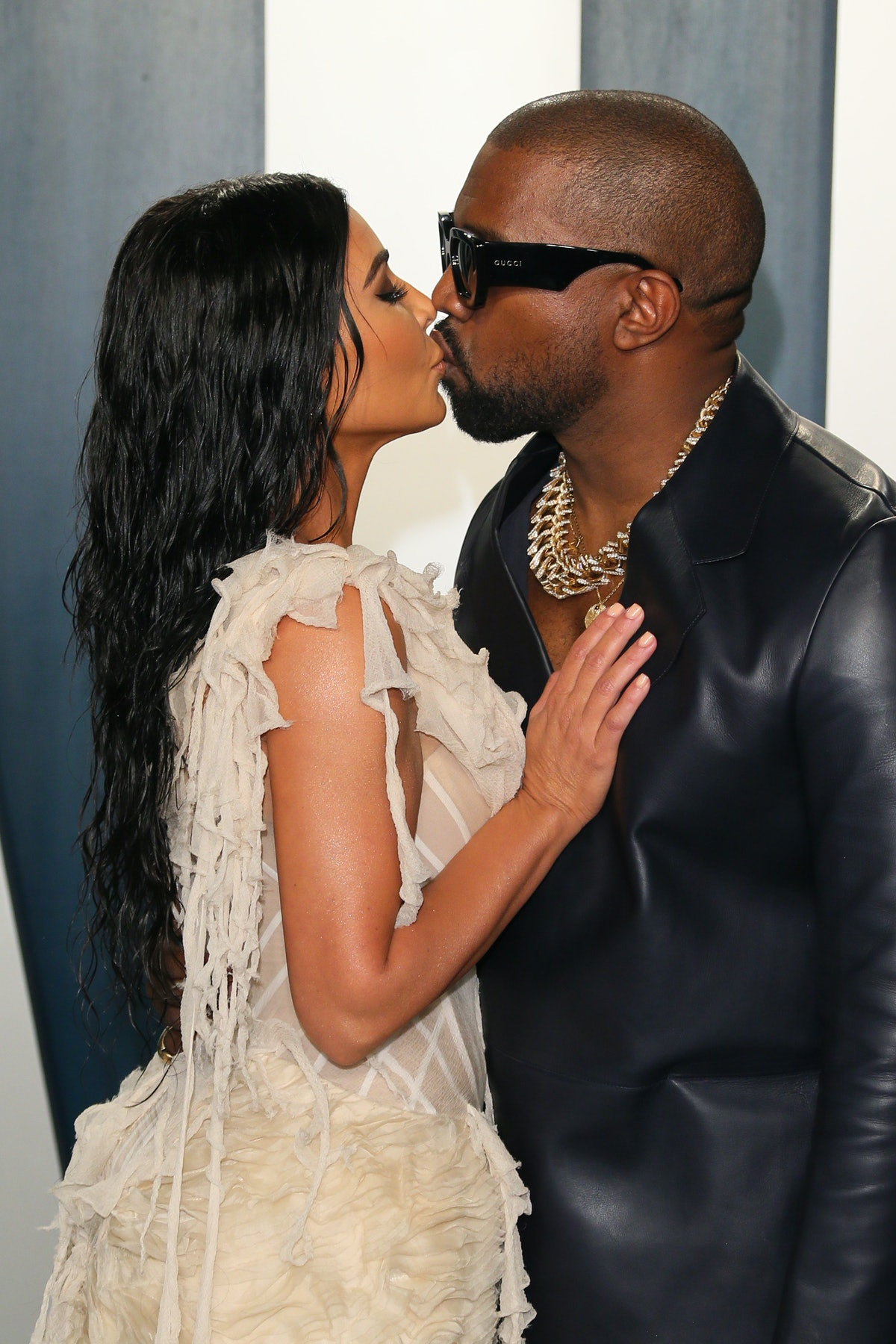 West and Kardashian kiss each other at a red carpet event.