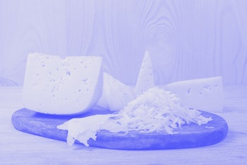 Pieces of cheese and grated cheese on the wooden board. Dutch cheese texture. Concept of healthy and...