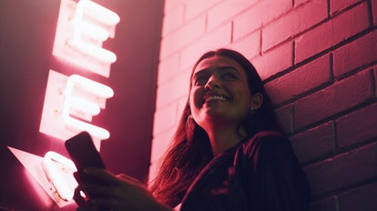 Shot of a young woman using her cellphone while outside a building at night