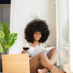A smiling Black woman with a large Afro sits near a bright window, reading a book and drinking a gla...