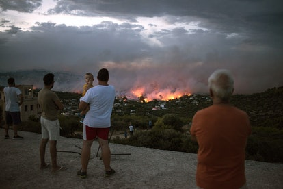 People watch a wildfire in the town of Rafina, near Athens, on July 23, 2018