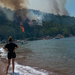 A woman watches the forest burn from a beach in Mugla, a Marmaris' district, as Turkey struggles aga...