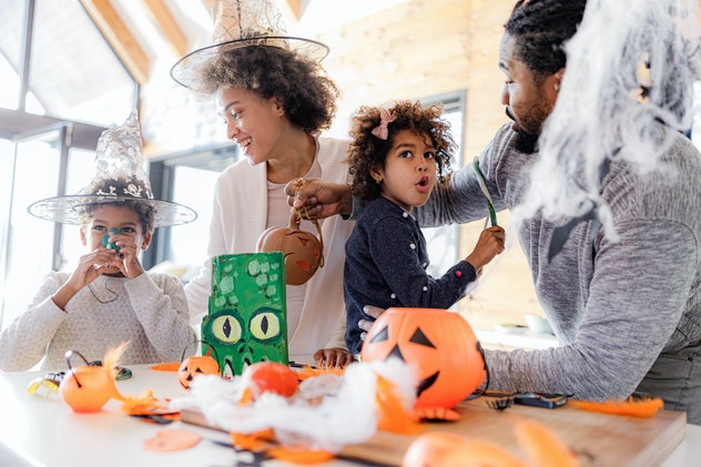 Happy black parents and their kids enjoying during Halloween celebration at home.