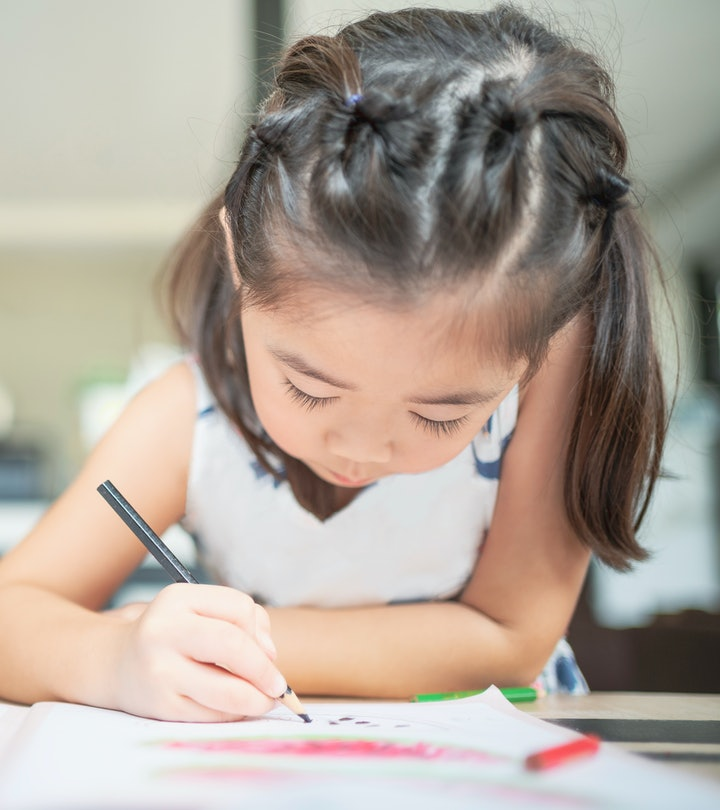 Young girl coloring with colored pencil