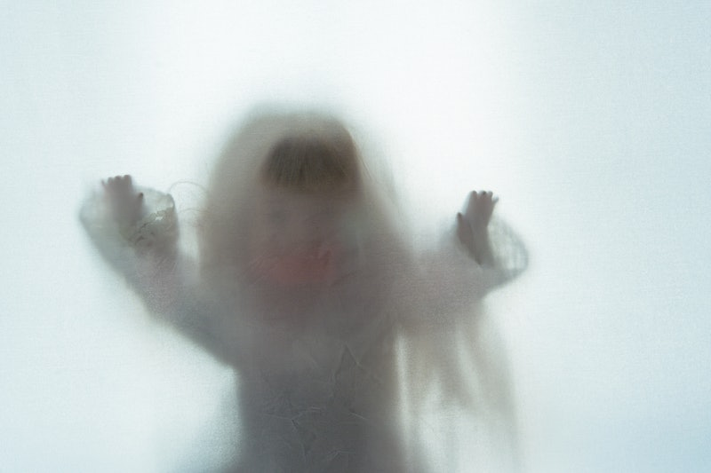 A scary edit of an old doll holding its hands up, shot through a semi transparent material. Creating...