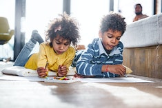 Two kids lying on the floor, coloring on pieces of paper