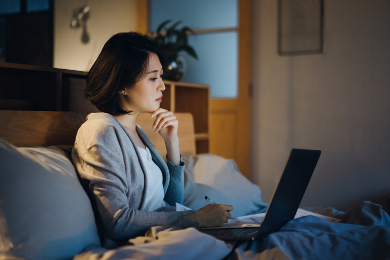 Busy young Asian woman sitting on bed, working from home using laptop and handling paperworks till l...