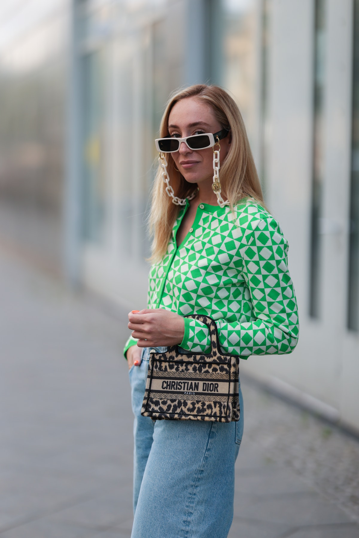 BERLIN, GERMANY - AUGUST 03: Sonia Lyson wearing Dior mini bag, green and white Zara cardigan, & oth...