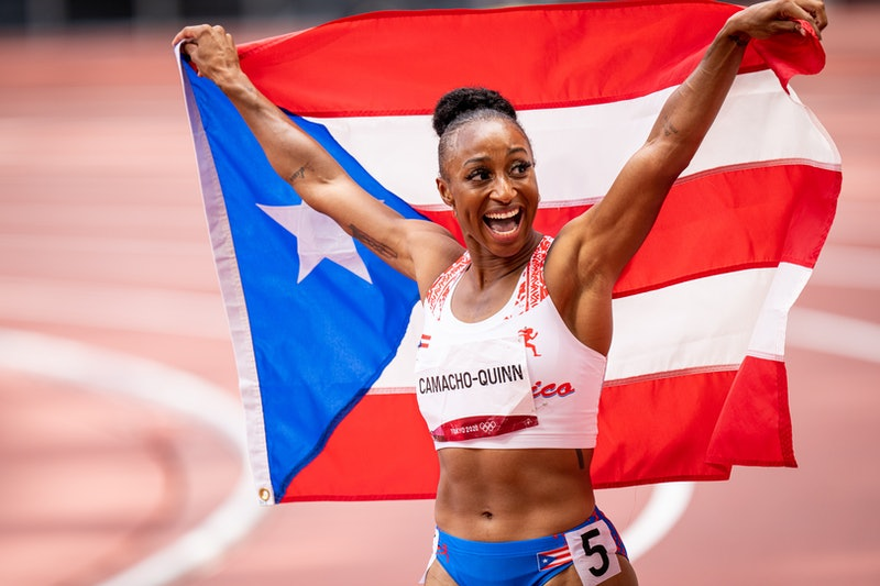 Jasmine Camacho-Quinn poses with the Puerto Rican flag after competing in the Women's 100m Hurdles F...